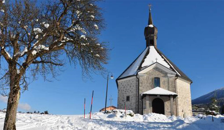 Kirche in Loibichl in winterlicher Landschaft und einem teilweise mit Schnee bedeckten Baum auf der Seite. (© Christine Steger)