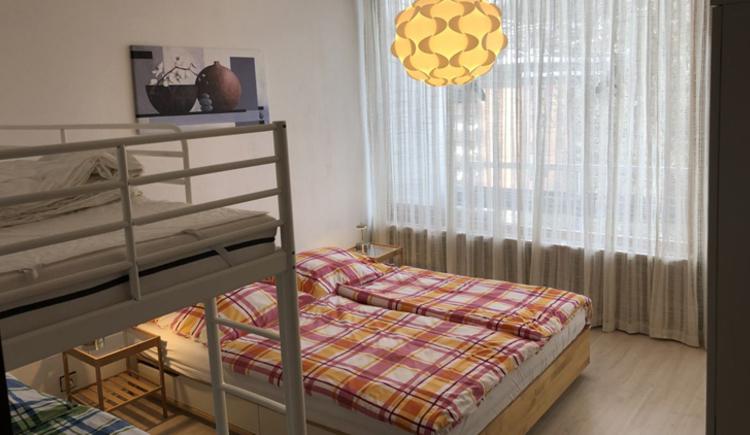 Schlafzimmer mit einem Doppelbett und einem Stockbett
