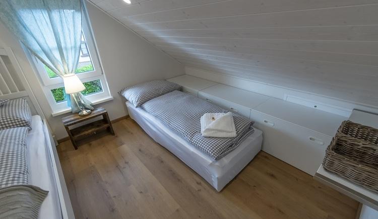 Die Mansarde des Obergeschosses sorgt für eine gemütliche Atmosphäre im Schlafzimmer.