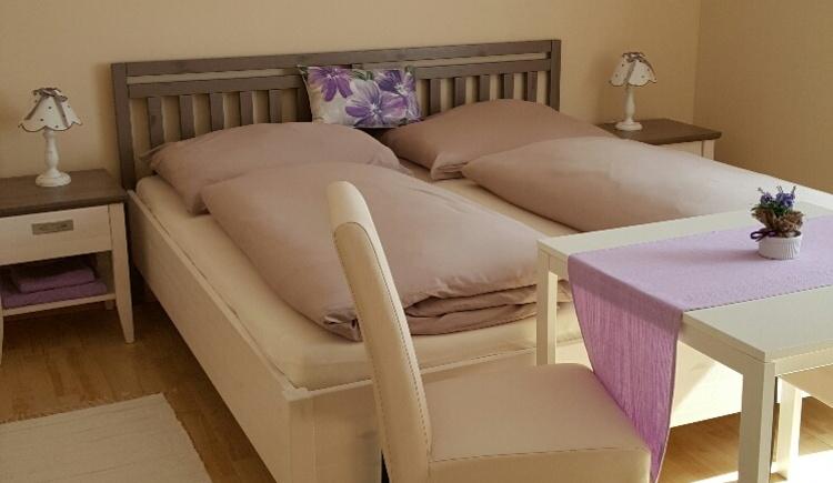 Das Bild zeigt ein liebevoll aufgebettetes Schlafzimmer mit einem kleinen Tisch am Fußende. (© Promberger Alfred)