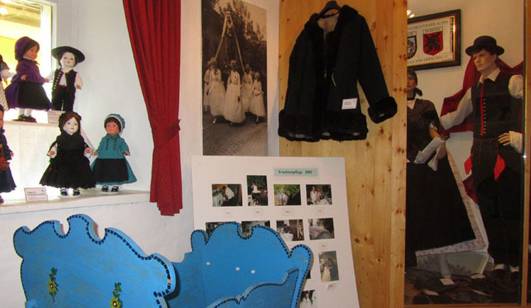 Ausstellungsstücke wie Puppen, Tracht und eine alte Wiege. (© Tourismusverband MondSeeLand)