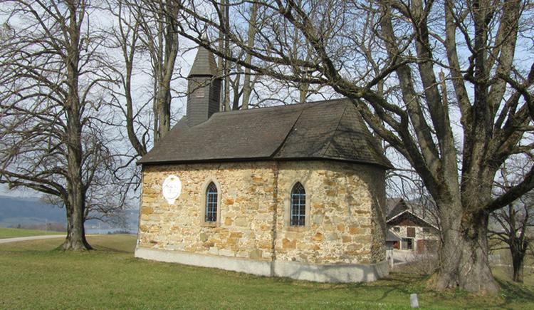 Kapelle umgeben von Wiese und Bäumen ohne Blätter. (© www.mondsee.at)