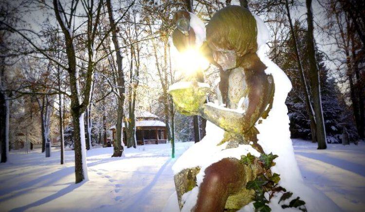 Das Brunnenweibchen im Kurpark Bad Hall. Hier im Foto schneebedeckt. Im Hintergrund kahle Bäume und die Wintersonne hell strahlend. (© Holnsteiner)