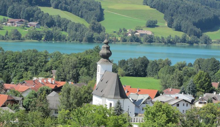 Blick auf die Kirche umgeben von der Landschaft und dem See