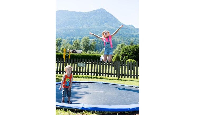 Kinder hüpfen in einem Trampolin. (© Ellmauer)