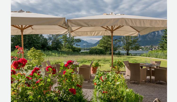 im Vordergrund Rosensträucher, dahinter gemütliche Stühle, gedeckter tisch mit Gläser, Sonnenschirme, im Hintergrund eine Wiese, Bäume, der See und die Berge. (© Lackner)