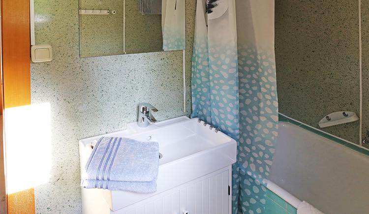 Badezimmer mit Waschbecken, Spiegel, Badewanne