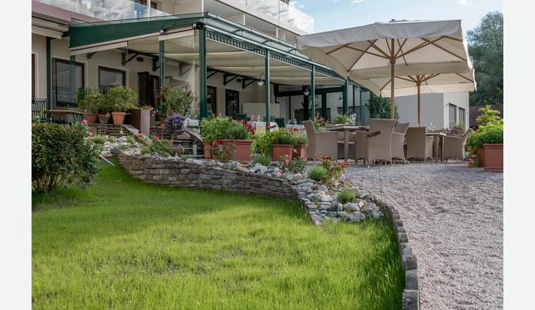 Blick auf die Terrasse und den Wintergarten, mit Stühlen, Tischen, Sonnenschirmen, Pflanzen. (© Lackner)