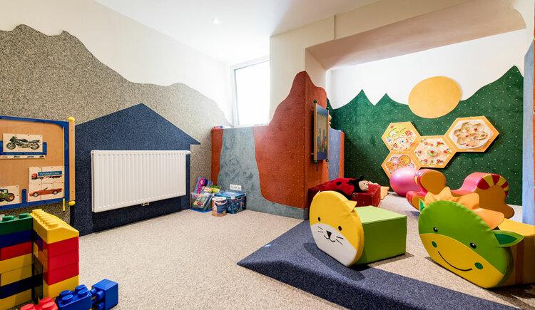 große Bausteine, Sitzkissen in Tierform, Motorikspiele an der Wand. (© Hotel Krone)