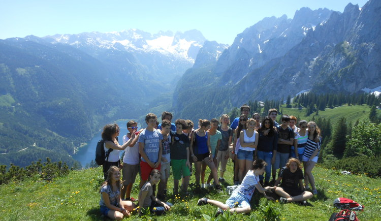 A group made a picture in front of the panorama view of the Dachstein and the Gosausee.