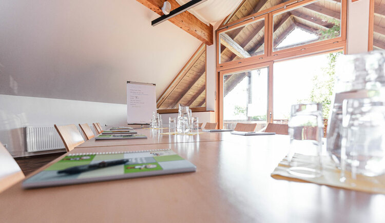 Seminarraum mit Schreibutensilien am Tisch, Wasserkaraffe und Gläser. (© Seminar- und Biobauernhof Aubauer)