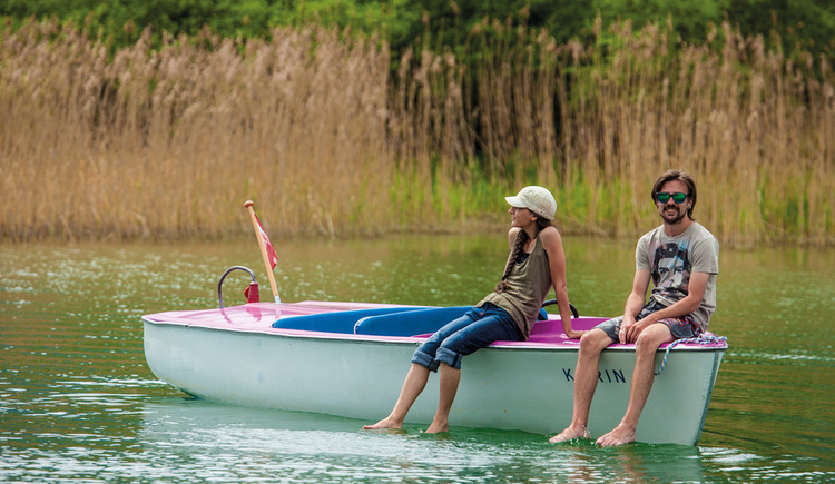 A man and a woman are sitting on an electro boat, with their feet in the lake. (© Mondsee Schifffahrt Hemetsberger)