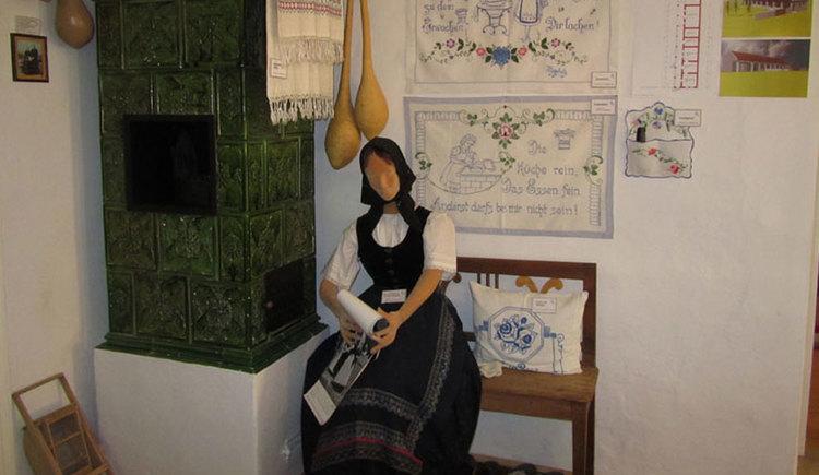 Eine Puppe in Tracht sitzt neben dem Kamin im Museum, an der Wand hinter ihr sind alte Stickereien. (© Tourismusverband MondSeeLand)