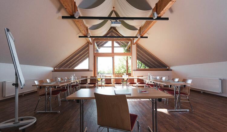 Seminarraum mit Schreibutensilien am Tisch, Wasserkaraffe und Gläser, Flipchart. (© Seminar- und Biobauernhof Aubauer)