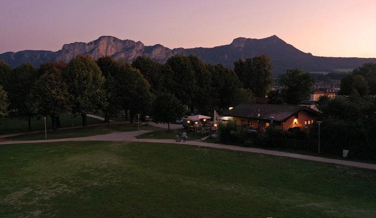 Seewiese, Pizzeria, dahinter Panorama und Sonnenuntergang. (© Peter Witzelsteiner)