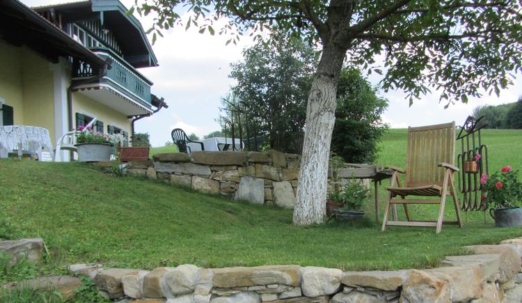Blick vom Garten, in der Wiese ein Sessel, im Hintergrund ein Teil vom Haus. (© Langwallner)