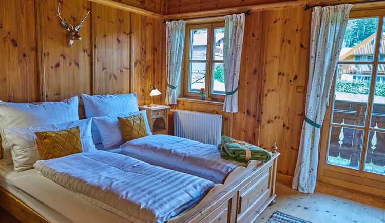 Das gemütliche Doppelzimmer ist mit viel Holz ausgestattet. (© Ewinger Lodge)