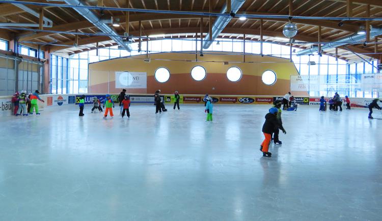 Personen beim Eislaufen in einer Halle