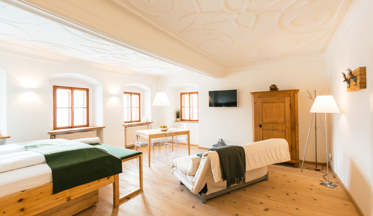 Royal Suite Wald Hallstatt Hideaway with a baroque wooden ceiling and four windows overlooking the lake. (© Hallstatt Hideaway)