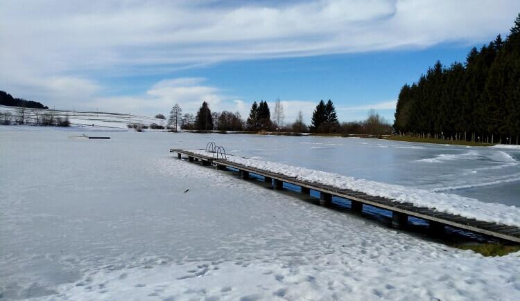 Innviertel-Tourismus   Kulturweg in PrametZu sehen ist der zugefrorene Prameter Badesee mit dem verschneiten Holzsteg. (© Innviertel-Tourismus)