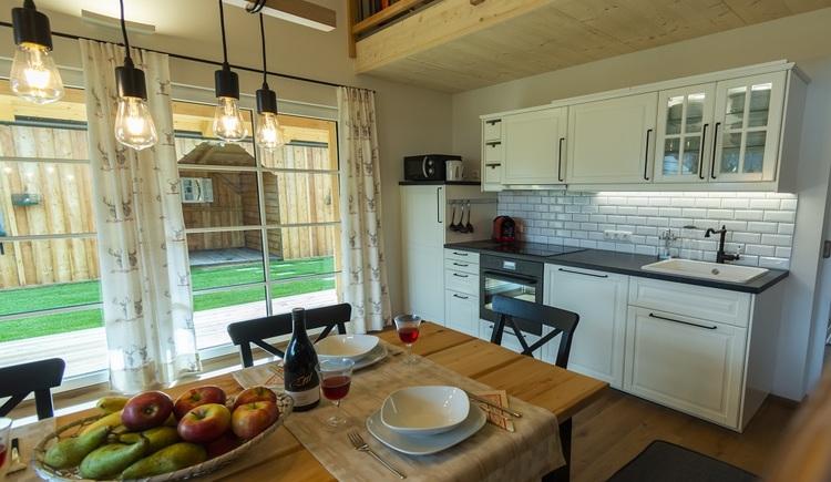 Der modern ausgestattete und in den Wohnraum des Chalets integrierte Küchen- und Essbereich lässt keine Wünsche offen.