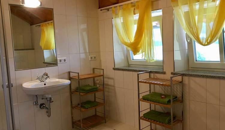 Bad mit Waschbecken, Spiegel, Regal und zwei Fenstern