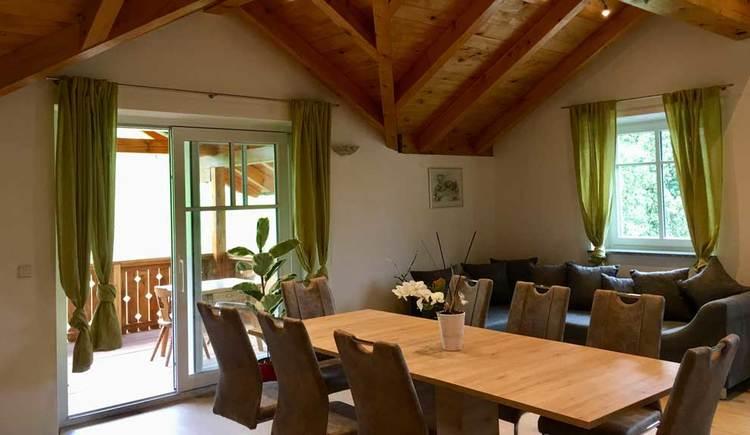 Wohnbereich mit großem Esstisch und Stühlen im Vordergrund, dahinter Couch und Fenster
