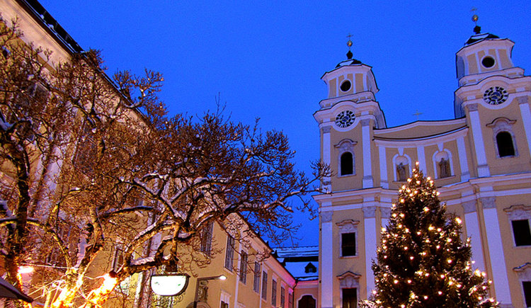View to the basilica St. Michael and the Christmas tree in front of the basilica. (© www.mondsee.at)