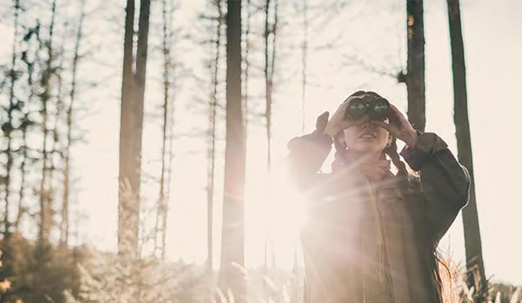 Bild zeigt Jägerin mit Fernglas.