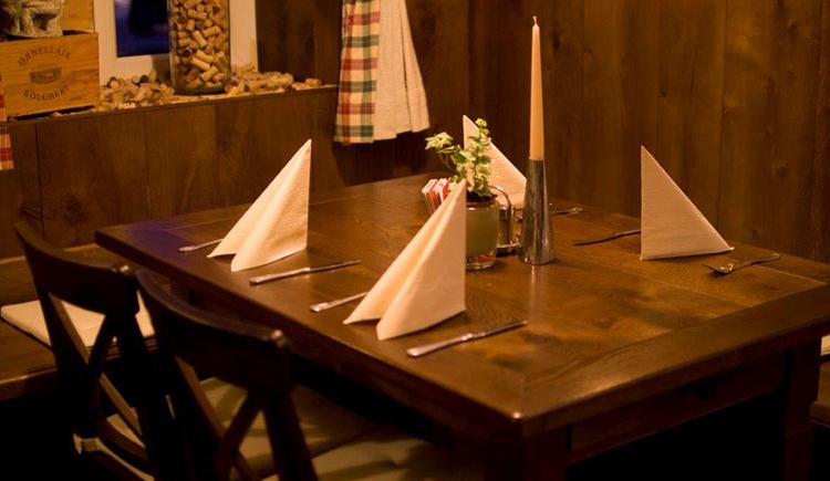 Tisch mit 4 Gedecken, Kerze und Blumenschmuck. (© Wirsthaus zur Westbahn)