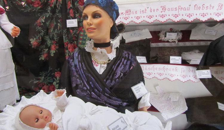 Eine Puppe (junge Frau) des Museums in traditioneller Kleidung hält eine Baby-Puppe im Arm. (© Tourismusverband MondSeeLand)