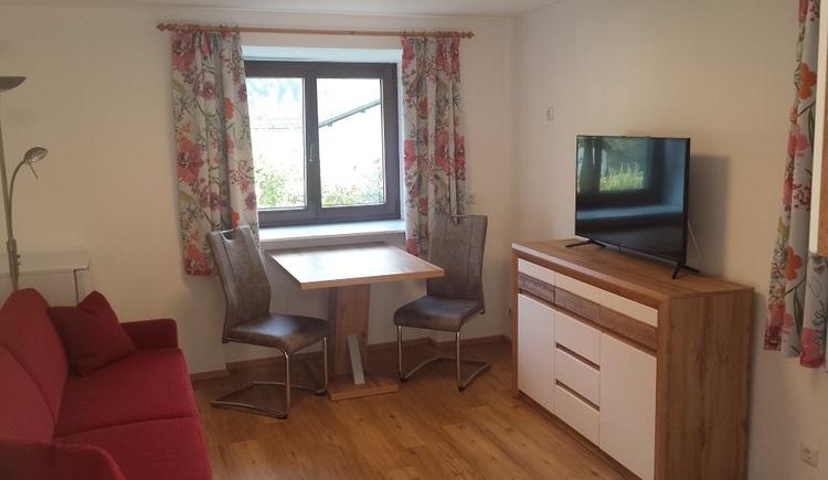 Zu sehen ist der gemütliche Fernseh- und Essbereich im Wohnraum der Ferienunterkunft Haus 66 in Obertraun. (© Johann Höll)