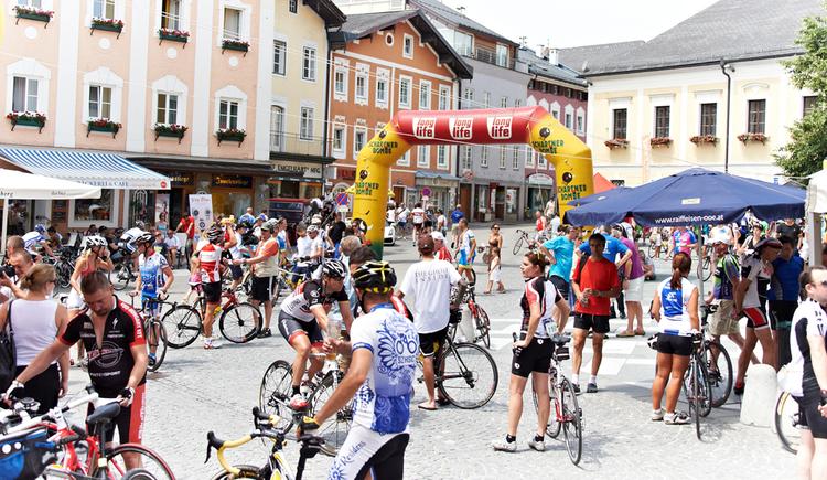 Zuschauer erwarten die Radrennfahrer beim Ziel, im Hintergrund Häuser. (© Marco Felgenhauer)