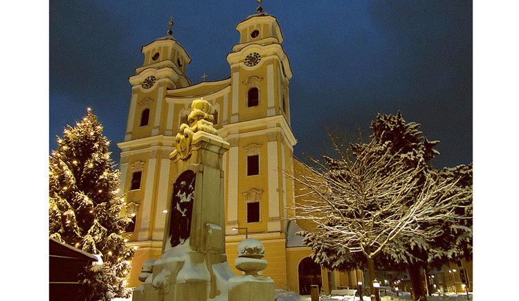 Sideward view to the basilica and a snow-covered tree as well as the huge Christmas tree in front of the basilica. (© TVB Mondsee-Irrsee)