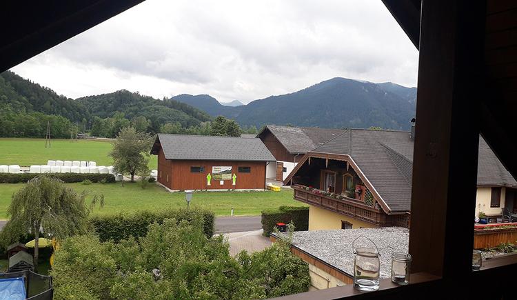 Blick vom Balkon auf die umliegenden Häusern, Berge, Wälder