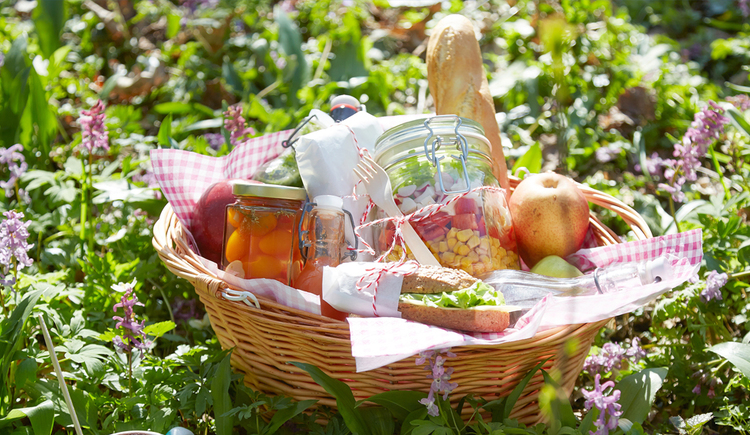 Filled picnic basket on a flowering meadow. (© Naturpark Attersee-Traunsee/Daniela Stockinger)