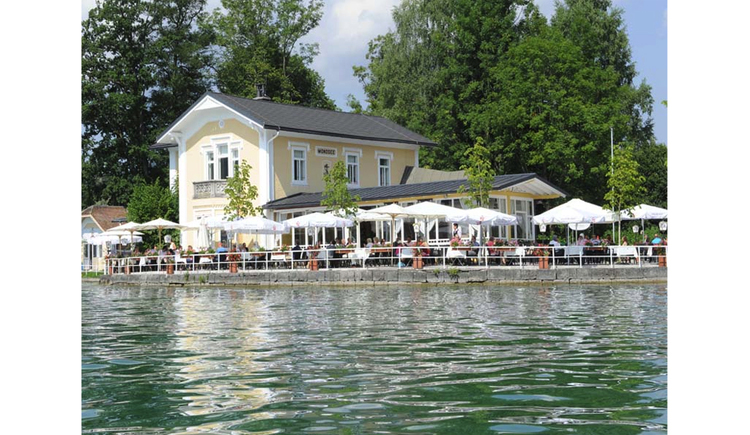 Blick vom See auf das Haus, im Vordergrund der Gastgarten mit Stühlen, Tischen, Sonnenschirme, im Hintergrund Bäume. (© Schwaighofer)