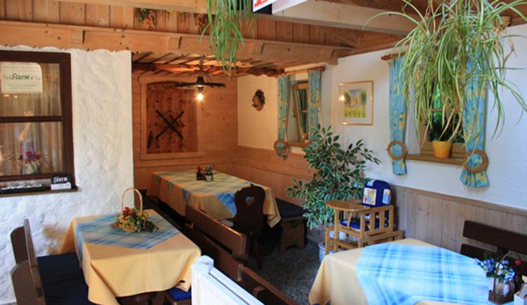 Blick in die Gaststube mit Tischen, Stühle, Eckbank, Pflanzen. (© Tourismusverband MondSeeLand)