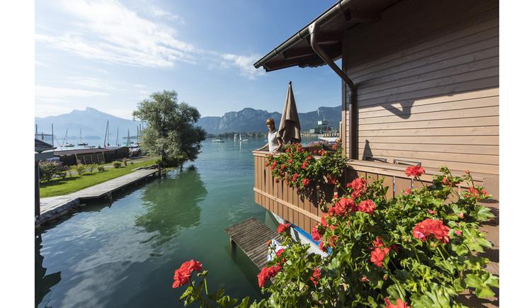 Blick auf den Balkon und See, im Vordergrund Blumen, im Hintergrund die Berge,. (© Seepension Hemetsberger)