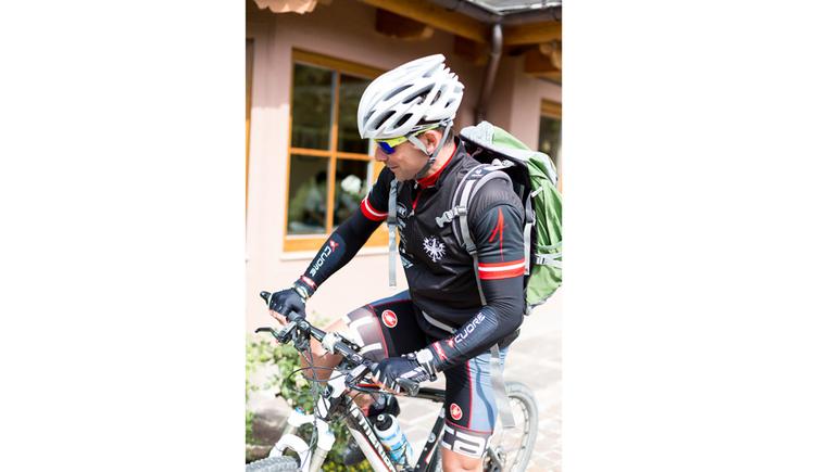 Person auf einem Fahrrad mit Helm und Rucksack. (© Ellmauer)