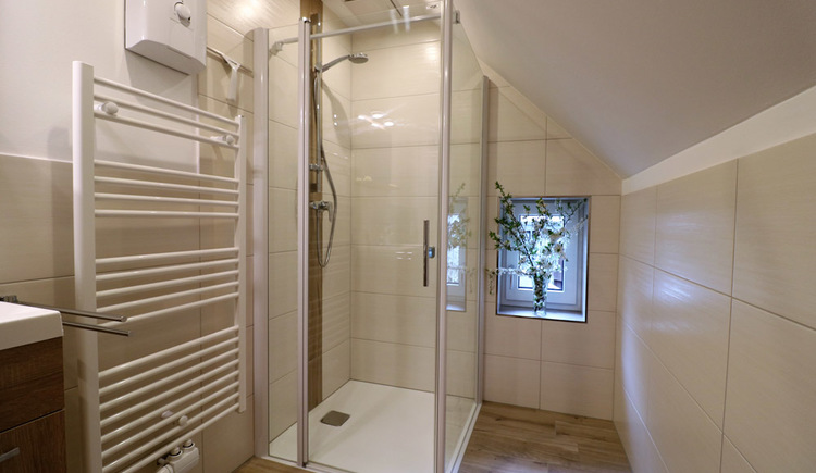 Bright and modern bathroom with shower cabin and towel dryer