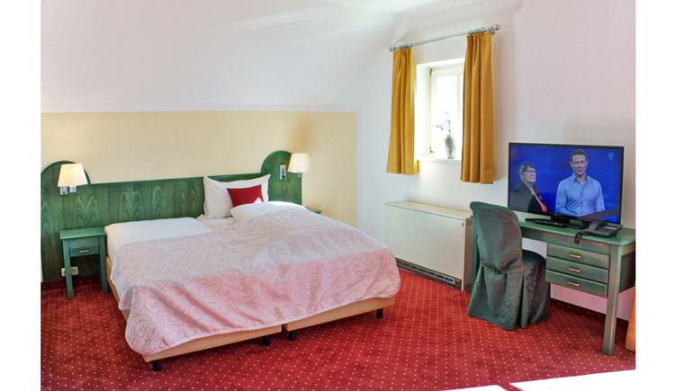 Doppelbett, Tisch, Stuhl, seitlich ein Fenster. (© Hotel Villa Drachenwand)