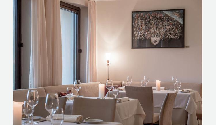 gedeckte Tische mit Gläser, Servietten, Teller, Besteck, Kerzen, Eckbank und Stühle, im Hintergrund ein Bild, seitlich Fenster. (© Lackner)