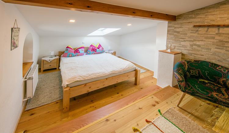 Das Schlafzimmer ist gemütlich mit viel Holz eingerichtet und verfügt über ein Doppelbett