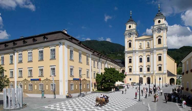 Blick auf die Basilika, im Vordergrund der Vorplatz, mit einem Brunnen, und einer Pferdekutsche. (© www.mondsee.at)