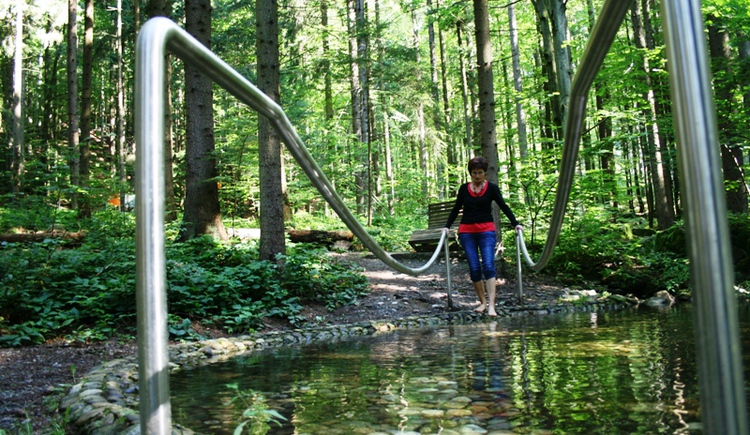 Wasserbecken mit Steinen indem eine Dame barfuß durchgeht. (© Ferienregion Böhmerwald)