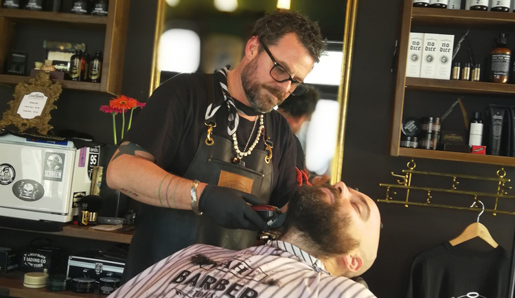 Person cuts the beard to a customer