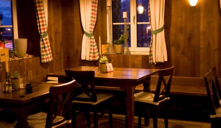 Blick in die Gaststube mit Tischen und Stühlen, im Hintergrund Fenster. (© Fam. Hitzl)
