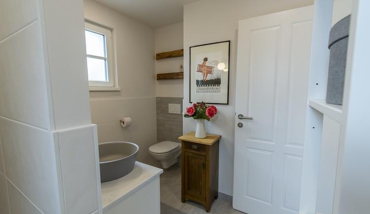 Die Badezimmer des Chalets sind in Weiß- und Grautönen gehalten und mit Dusche und WC ausgestattet. Altholzdetails verleihen ihnen den speziellen Charm.