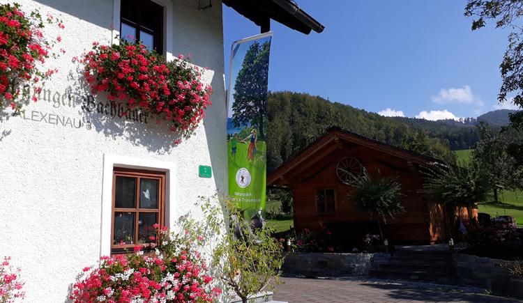 Hausbild Bachbauer in Weyregg am Attersee mit Naturparkfahne. (© Johanna Kiebler)